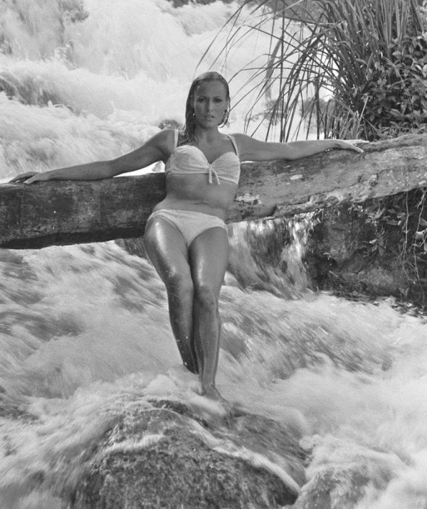 ca. 1962, Jamaica --- Swiss actress Ursula Andress poses in a rushing stream during the filming of the James Bond movie in Jamaica. --- Image by © Bradley Smith/CORBIS